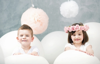 Adorable kids playing giant white balloons
