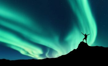 Northern lights and silhouette of standing man with raised up arms on the mountain peak in Norway. Aurora borealis and happy man. Sky with stars and green polar lights. Night landscape with aurora