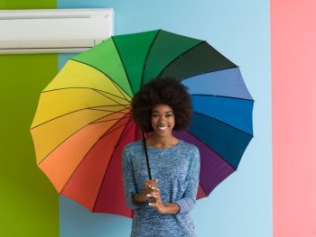 Portrait of young beautiful african american woman holding a colorful umbrella isolated on a Colorful background
