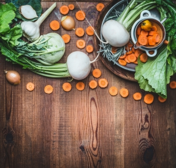Food background with organic local vegetables for healthy clean eating and cooking on rustic wooden , top view, place for text. Vegan or vegetarian food concept