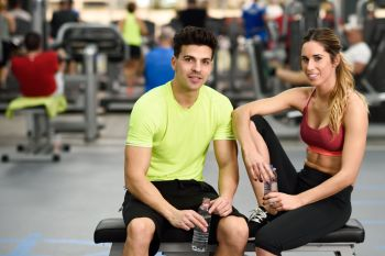 Handsome man and beautiful sporty woman drinking water after workout in the gym