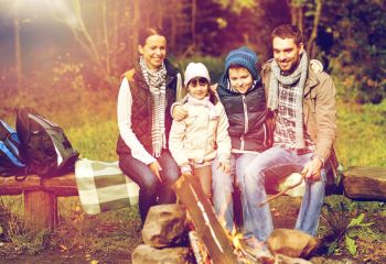 travel, tourism, hike and people concept - happy family sitting on bench at camp fire in woods. happy family sitting on bench at camp fire