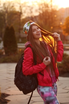 Portrait of a beautiful young traveler woman with a backpack, bright orange sunset light, traveling along Europe, freedom and active lifestyle concept