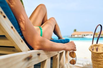 Young woman at beach on wooden sun bed loungers. Summer vacation at Maldives.
