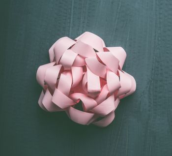 Pastel pink bow on gray background, creative holiday layout, top view
