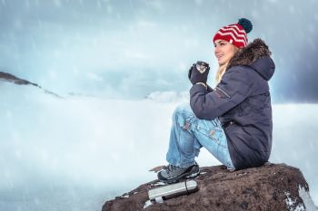 Traveler woman sitting on the big stone with mug of hot tasty mulled wine in hands enjoying view on snowy mountains, having fun outdoors in cold wintertime day, active winter vacation