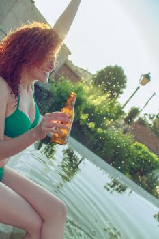 Young woman enjoying a beer in a summer party