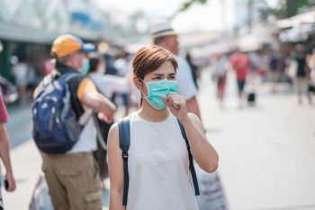 young Asian woman wearing protection mask against Novel coronavirus (2019-nCoV) or Wuhan coronavirus at Chatuchak Weekend Market, landmark and popular for tourists attractions in Bangkok, Thailand