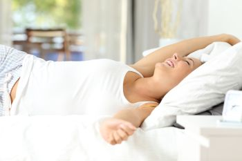 Happy woman stretching arms waking up on the bed at home