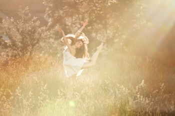 The ballerina doingis arabesk at the meadow In the white dress. At the nature background with the rays of sunset.