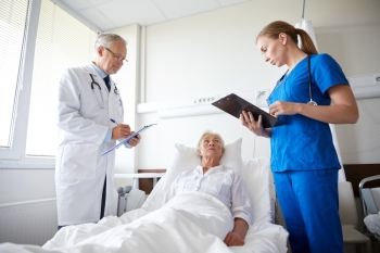 medicine, age, health care and people concept - doctor and nurse with clipboards visiting senior patient woman at hospital ward