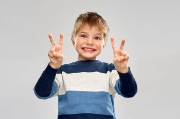 childhood, gesture and people concept - portrait of smiling little boy in striped pullover showing peace hand sign over grey background. little boy in striped pullover showing peace