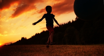 Small child playing ball on the field