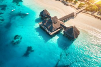 Aerial view of beautiful hotel on the water in ocean at sunset in summer. Zanzibar, Africa. Top view. Landscape with wooden hotel on the sea, azure water, sandy beach, green palm trees. Luxury resort