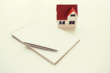 building, mortgage, real estate and property concept - close up of house model, notebook and pencil. close up of house model, notebook and pencil. close up of house model, notebook and pencil