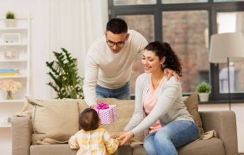 family, holidays and people concept - happy mother, father and baby daughter with birthday present at home. happy family with birthday present at home