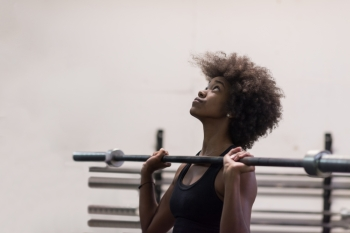 Young Cute african american sport woman in fitness room lifting empty bar
