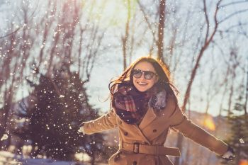 Portrait of a pretty girl with pleasure spending time on bright sunny day in winter park, having fun like a child, happy wintertime vacation