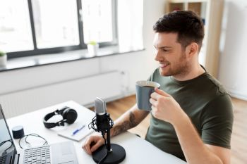 technology, mass media and podcast concept - happy male audio blogger with laptop computer and microphone drinking coffee and broadcasting at home office. blogger with laptop and microphone audio blogging