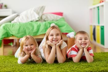 childhood, leisure and family concept - happy little kids lying on floor or carpet. happy little kids lying on floor or carpet. happy little kids lying on floor or carpet