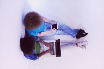 startup business and new mobile technology concept with young multiethnic couple in modern bright office interior working on laptop and tablet computer on new creative project and brainstorming top view