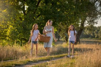 Toned image of happy family walking at meadow to picnic