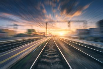 Railway station with motion blur effect. Blurred railroad. Industrial conceptual landscape with blurred railway station, buildings, blue sky with colorful clouds and sun. Railway track. Background. Railway station with motion blur effect. Blurred railroad