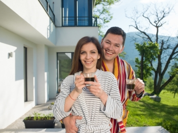 Young beautiful couple in bathrobes are enjoying morning coffee in front of their luxury home villa