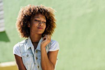 Young black woman, afro hairstyle, in the street. Girl, model of fashion, wearing casual clothes in urban background.
