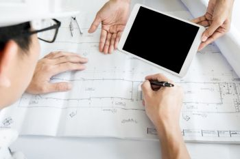 Two colleagues discussing data working and tablet, laptop with on on architectural project at construction site at desk in office.