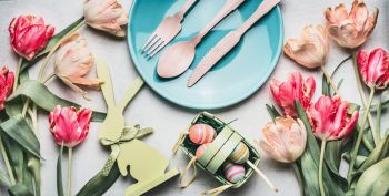 Easter composing with spring tulips , bunny decor, eggs and festive table setting with plate and cutlery, top view, banner
