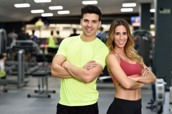 Man and woman personal trainers in the gym. Young girl and guy wearing sportswear with arms crossed.