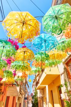Street decorated with umbrellas of different colours in Aegina town on summer sunny day, Aegina island, Greece