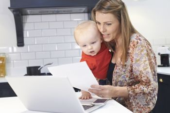 Busy Mother With Baby Coping With Stressful Day At Home