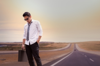 Asian Businessman tired and standing on road at upcountry out of modern city, travel concept