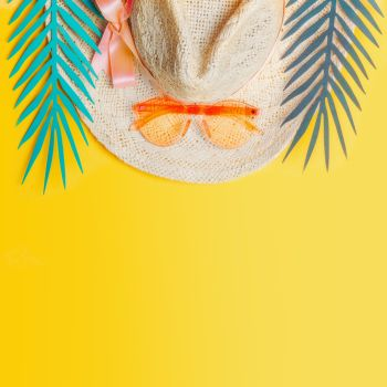 Straw hat with orange sunglasses and tropical leaves on yellow background, top view. Summer holiday concept. Tropical vacation . Flat lay. Copy space