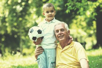 happy grandfather and child have fun and play in park on beautiful  sunny day. grandfather and child have fun  in park