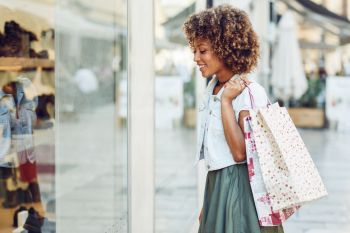 Young black woman, afro hairstyle, looking at a shop window. Young black woman in front of a shop window in a shopping street. African girl with afro hairstyle wearing casual clothes.