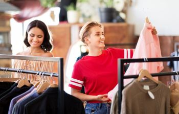 sale, shopping, fashion and people concept - happy young women choosing clothes at vintage clothing store. women choosing clothes at vintage clothing store