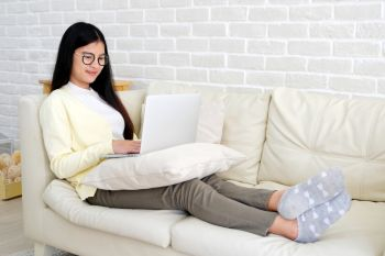 Young asian woman using laptop computer sitting  on sofa at home living room background, working at home, people and technology, lifestyles, education, business concept