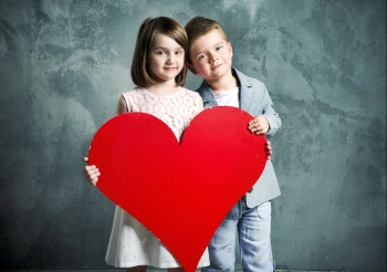 Two kids holding a giant paper heart