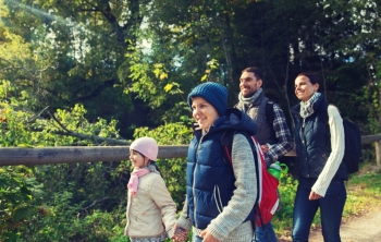 adventure, travel, tourism, hike and people concept - happy family walking with backpacks in woods. happy family with backpacks hiking in woods
