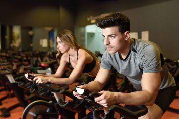 Attractive woman and man biking in the gym, exercising legs doing cardio workout cycling bikes. Couple in a spinning class wearing sportswear.