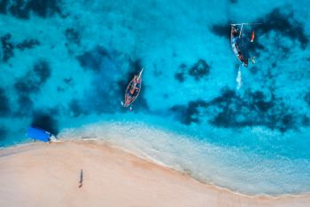 Aerial view of the fishing boats in clear azure water at sunrise in summer. Top view from drone of boat, blue sea, sandy beach, walking people. Indian ocean. Travel. Tropical seascape with motorboat
