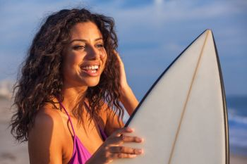 Beautiful young woman surfer girl in bikini with surfboard standing on a beach at sunset or sunrise