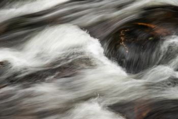 Detail landscape image of river flowing over rocks with long exposure motion blur