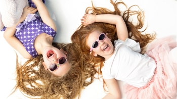 Two laughing kids lying on a white floor