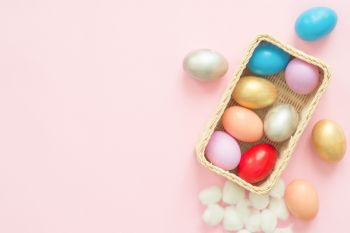 Flat lay top view colorful easter egg painted in pastel colors composition on pink pastel color background. Easter day background top view with copy space.