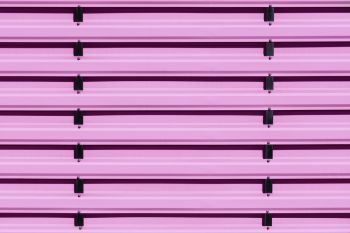 Pink siding metal fence is made of steel planks with vertical black guides. Iron fence painted in pink color, background, close-up.. Pink metal protective fence with vertical guides.