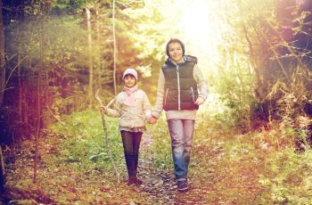 childhood, hiking and family concept - two happy kids walking along forest path. two happy kids walking along forest path